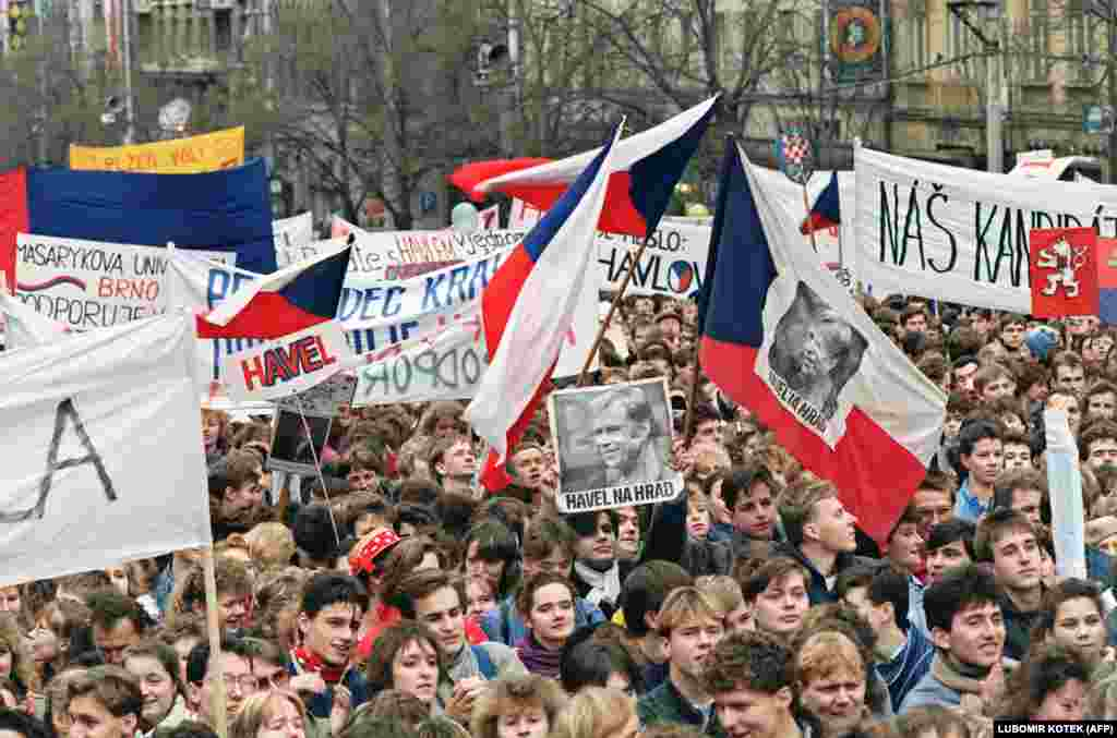 "Huge crowds continued to gather after the communists backed down and agreed to free elections. At this protest, on Wenceslas Square on December 19, 1989, a banner reads ""Havel na Hrad"" (Havel to the Castle), a popular slogan of the time in support of Havel becoming president."