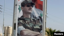 A picture of Syrian President Bashar al-Assad is seen at one of the entrances to the city of Homs in mid-June.