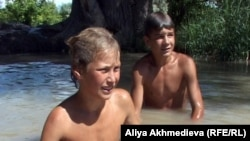 Дети купаются в поливном канале. Алматинская область, Уштобе, 14 июня 2011 года.
