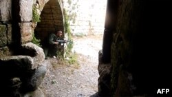 A Syrian rebel takes a position at the Crac des Chevaliers near the village of Azzara on the outskirts of the flashpoint city of Homs.