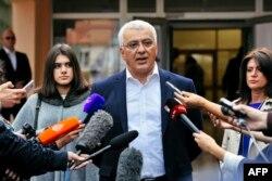 Andrija Mandic, leader of the Democratic Front, speaks to journalists after voting.