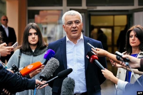Andrija Mandic, leader of the Democratic Front, speaks to journalists after voting.