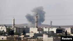 O coloană de fum în spatele unei moschei în orașul sirian Kobani de la granița cu Turcia 9 octombrie 2014.