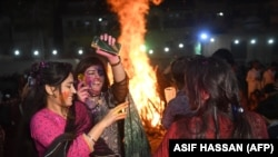 Pakistani Hindu women dance covered in colored powder as they celebrate the Holi festival in Karachi on March 20.