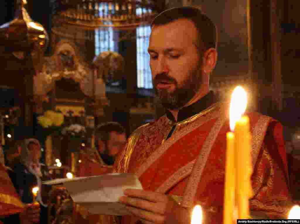 Священик зачитує імена українських журналістів, які віддали життя, виконуючи службовий обов'язок