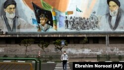 A man crosses an empty street under portraits of the late Iranian revolutionary founder Ayatollah Khomeini, right, and Supreme Leader Ayatollah Ali Khamenei, left, in Tehran, April 3, 2020