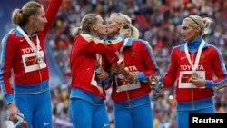 Спортсменки Ксения Рыжова и Татьяна Фирова (в центре) целуются на подиуме после победы на чемпионате мира по легкой атлетике в Москве. 17 августа 2013 года.