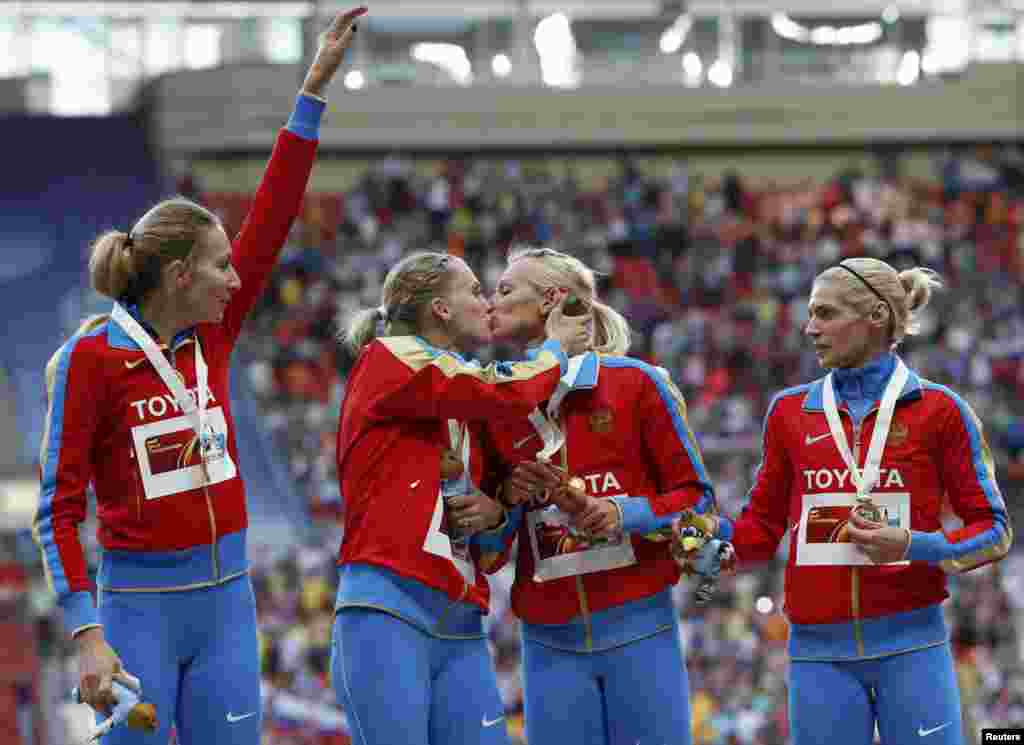 "Members of Russia's 4x400 women's relay team celebrate their gold medal at the IAAF World Athletics Championships in Moscow. There has been widespread speculation that the kiss between Ksenia Ryzhova (left center) and Yulia Gushchina was in protest to Russia's controversial law banning so-called ""homosexual propaganda."" The two have not commented. The other members of the winning team were Tatiana Firova (left) and Antonina Krivoshapka (right). (Reuters/Grigory Dukor)"