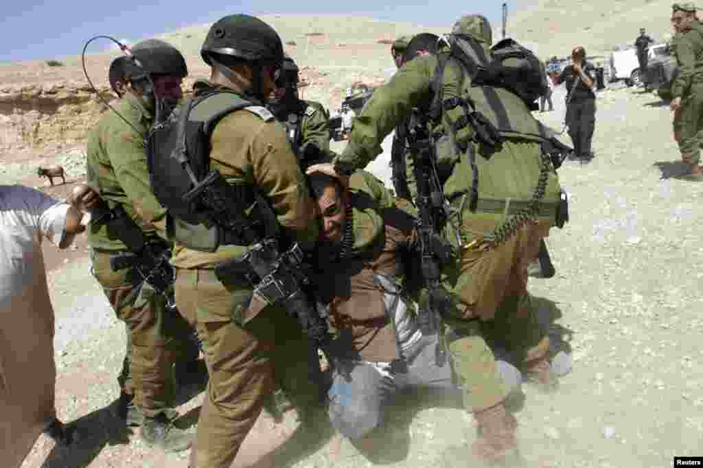 Israeli soldiers detain a Palestinian man during scuffles following an attempt by European diplomats to deliver goods to locals in the West Bank herding community of Khirbet al-Makhul. (Reuters/Abed Omar Qusini)