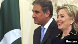 U.S. Secretary of State Hillary Clinton and her Pakistani counterpart, Shah Mehmood Qureshi, arrive for a meeting at the State Department in Washington today.
