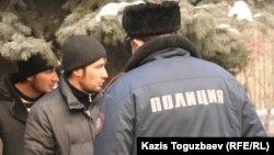 Алматыдағы әкімшілік сот алдында тұрған өзбек босқындары мен полицей. (Көрнекі сурет)
