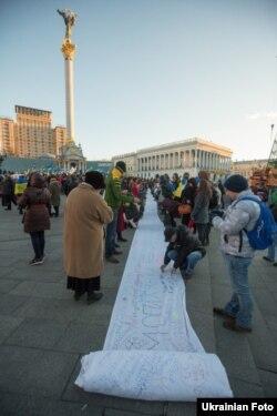 Учасники мітингу за євроінтеграцію на майдані Незалежності в Києві підписують лист президентові на полотні