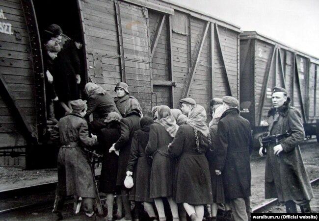 Майбутні остарбайтери біля вагонів перед відправленням до Німеччини, 1942 рік. Фото з виставки «Тріумф людини. Мешканці України, які пройшли нацистські концтабори»