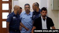 File photo:ISRAEL -- Gonen Segev, a former Israeli cabinet minister indicted on suspicion of spying for Iran, is escorted by prison guards as he arrives to court in Jerusalem on July 5, 2018.