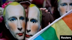 Протестующие в масках с изображением Владимира Путина у российского посольства в Лондоне во время митинга за права сексуальных меньшинств в России. 14 февраля 2014 года.