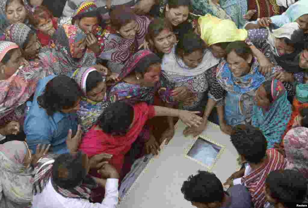 Family members mourn as they gather near the body of a relative, who was killed in a blast outside a public park in Lahore on March 27. (Reuters/Mohsin Raza)