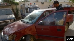 A Pakistani police officer inspects a vehicle in which an American woman was shot in Karachi on April 16.