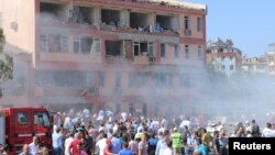 People rush to the scene of a bomb blast near a police station in the eastern Turkish city of Elazig on August 18.