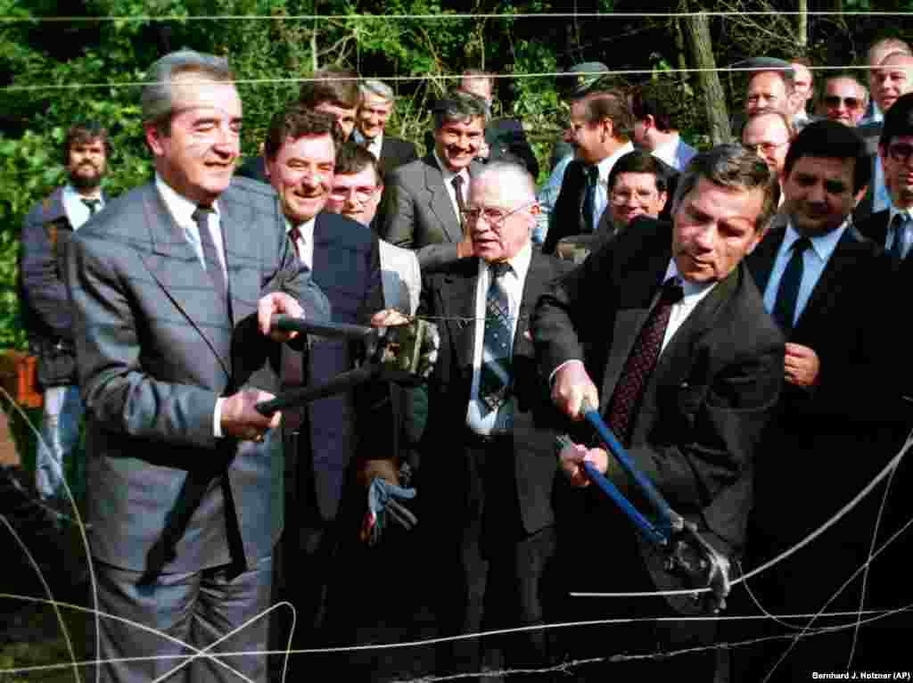Hungarian Foreign Minister Gyula Horn (right) and his Austrian counterpart, Alois Mock, cut through the barbed wire marking the border in Sopron, Hungary, on June 27. The symbolic gesture was made to highlight Hungary's decision to begin dismantling its border surveillance.