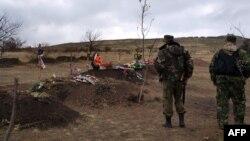 Пророссийские сепаратисты стоят у могилок. Донецкая область, 20 ноября 2014 года.