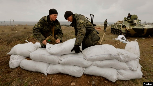 Ukrainian soldiers fortify a position with sandbags at a Ukrainian ...
