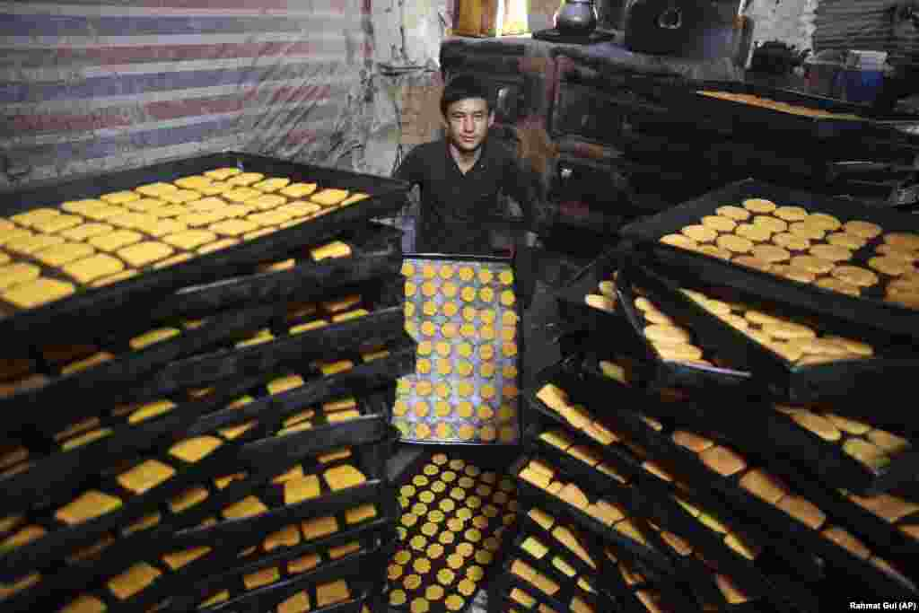 An Afghan boy makes sweets at a traditional bakery for the Eid al-Fitr holiday in Kabul on May 22.