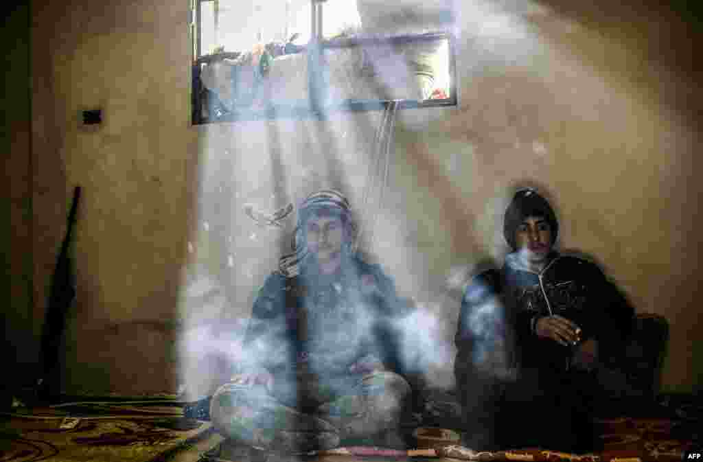 Kurdish fighters rest in a house on the outskirts of the Syrian town of Kobani. (AFP/Yasin Akgul)