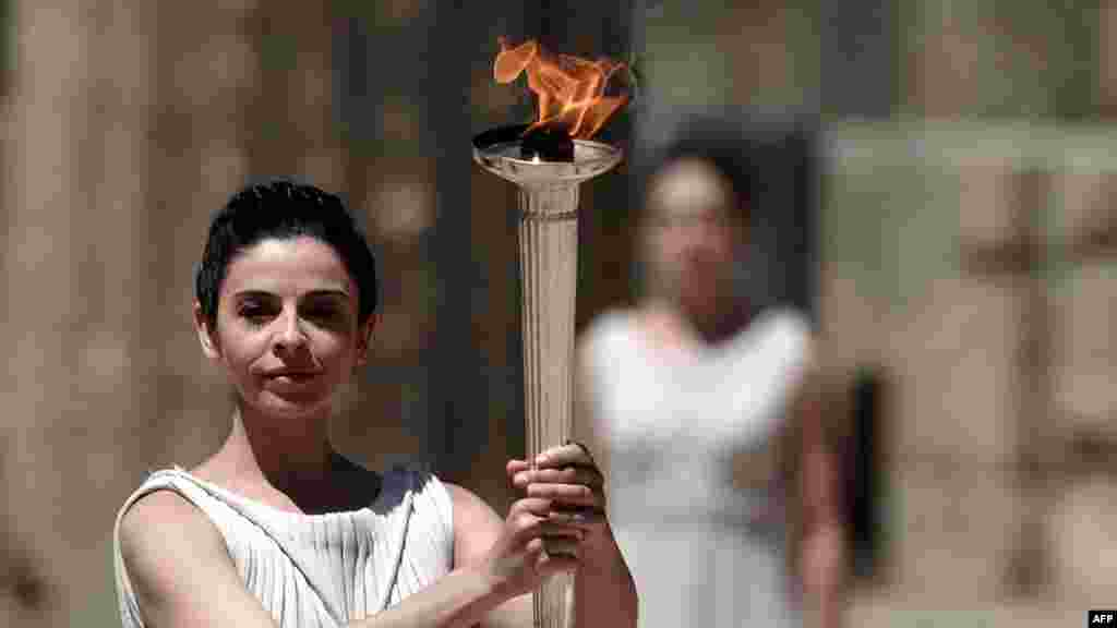 Actress Ino Menegaki, playing the role of high priestess, holds up the Olympic flame during a dress rehearsal for the torch-lighting ceremony of the London 2012 Olympic Games at the site of ancient Olympia on May 9.