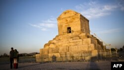 An Iranian family poses for a picture next to the tomb of Cyrus II of Persia, known as Cyrus the Great, the founder of the Persian Achaemenid Empire in the sixth century BCE, in the town of Pasargad.
