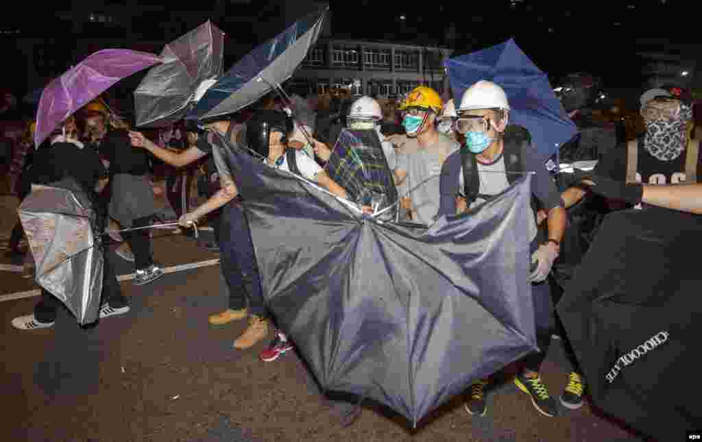 Pro-democracy protesters defend themselves with umbrellas against the police on Lung Wo Road, next to the Hong Kong Chief Executive's Office, part of the Central Government Office complex that the protesters are trying to surround. (epa/Alex Hofford)