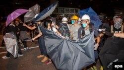 معترضان هوادار دمکراسی با چتر در مقابل پلیس از خود دفاع می کنند
