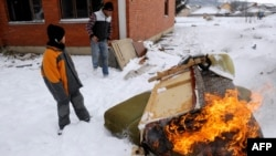 A child warms himself by a fire in a lead-contaminated Roma camp for internally displaced persons in northern Mitrovica in December 2012.