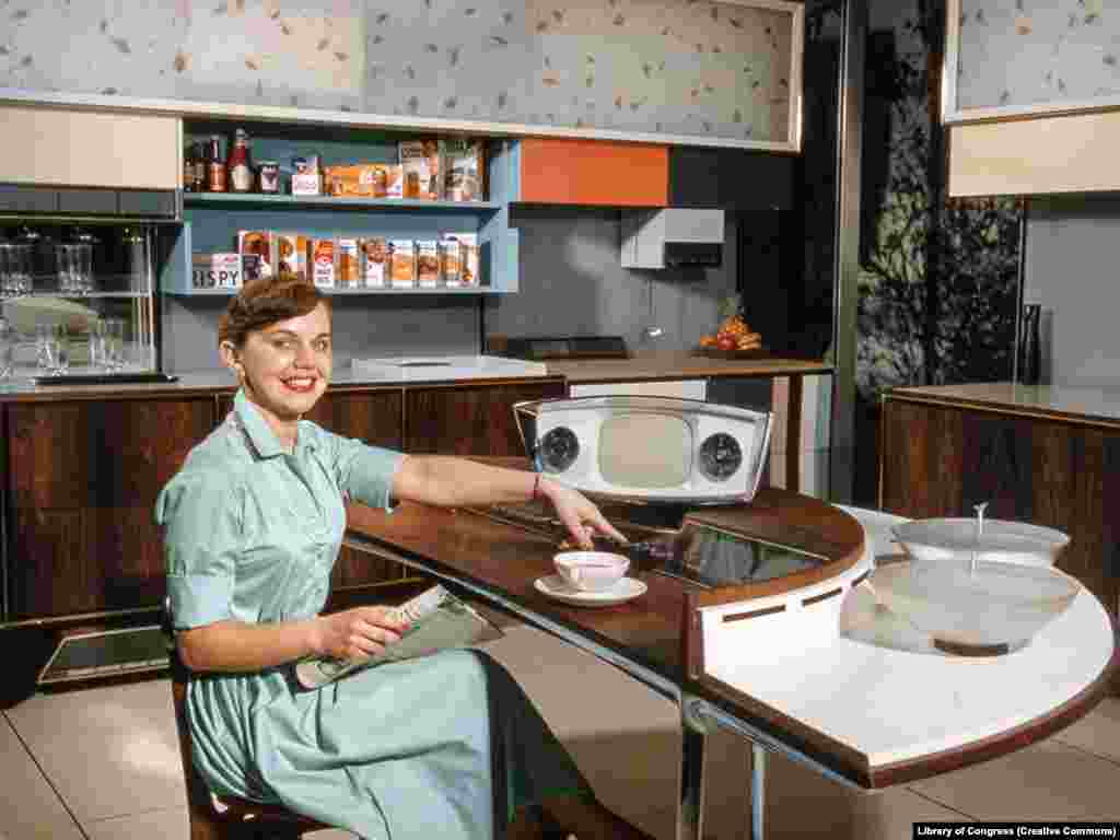 """A woman demonstrates a model kitchen made for the exhibition. During the debates, Nixon noted that conveniences like dishwashers made life """"more easy for our housewives,"""" to which Khrushchev countered, """"Your capitalistic attitude toward women does not occur under communism."""""""