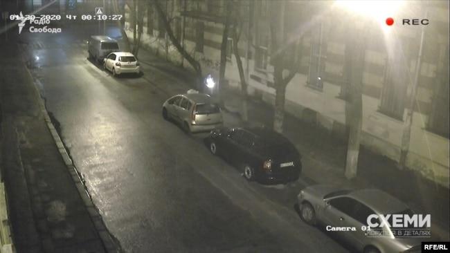 Щойно авто зникає за рогом, у кадрі з'являється особа з пакетом, зупиняється біля автівки Терещук і кладе пакет на капот