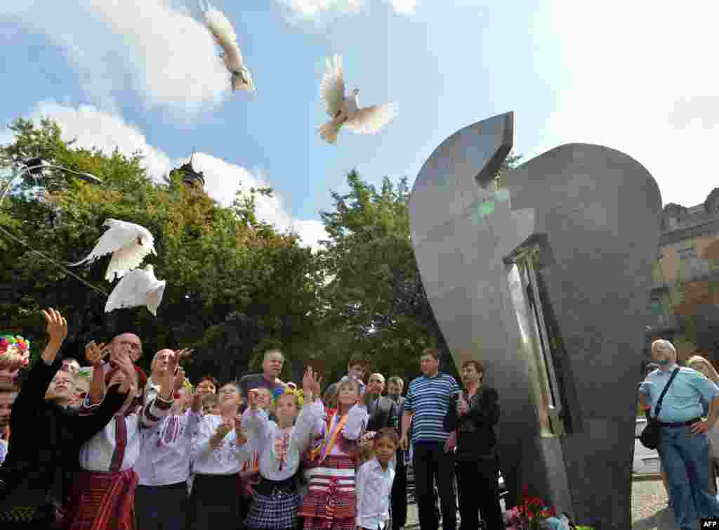 "Children release white doves in front of a monument to the victims of terrorism in Kyiv, Ukraine, on September 11, 2014. The monument, unveiled in 2005, is inscribed with the commandment ""Thou shalt not kill"" in 120 languages."