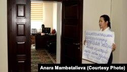 Анара Мамбеталиева в здании Госэкотехинспекции вышла на акцию с плакатом в руках.