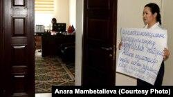 Анара Мамбеталиева иштеген мекемесинде плакат кармап пикетке чыккан.
