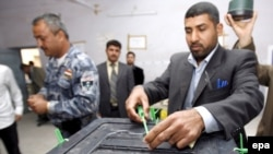 An electoral commission employee locks a ballot box at an Iraqi election center. (2009 file photo)