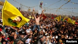 Demonstrators hold Kurdish flags and portraits of jailed Kurdistan Workers Party (PKK) leader Abdullah Ocalan during a gathering to celebrate Norouz in the southeastern Turkish city of Diyarbakir on March 21, 2013.