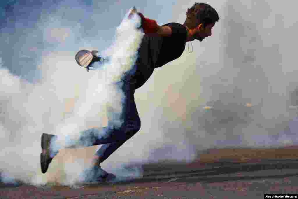 An Iraqi demonstrator runs as he carries a tear-gas canister during ongoing anti-government protests in Baghdad on November 14. (Reuters/Alaa al-Marjani)