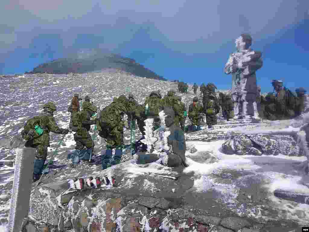 A handout picture provided by Japan's Self-Defense Forces shows Japanese Ground Self-Defense Force rescuers during a search-and-rescue operation near the peak of snow-covered Mount Ontake, which erupted on September 27. At least seven hikers are still missing on the volcano after it erupted unexpectedly. Fifty-six hikers died. (epa)