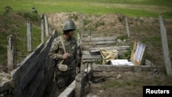 Nagorno-Karabakh -- An ethnic Armenian soldier stands guard in a trench at artillery positions near the Nagorno-Karabakh's town of Martuni, April 7, 2016