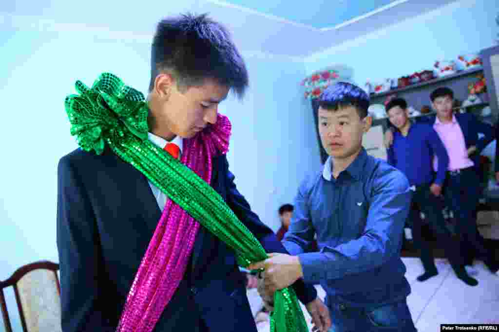 In the meantime, Shafur is getting ready to pick up the bride. Friends help to put red and green ribbons on his suit - the distinctive signs of the groom.