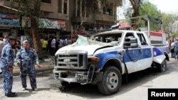 عناصر من الشرطة يتفحصون موقع تفجير في منطقة الكرادة ببغداد