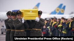Soldiers carry a coffin containing the remains of one of the 11 Ukrainian victims of the downed plane at Boryspil International Airport outside Kyiv.