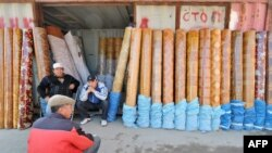 Traders sit outside a converted shipping container at a bazaar in southern Kyrgyzstan.