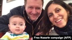 Iranian-British citizen Nazanin Zaghari-Ratcliffe (R) poses for a photograph with her husband Richard and daughter Gabriella, undated