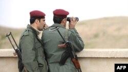 منتسبان لقوات الأمن العراقية يراقبان منطقة الحدود مع إيران