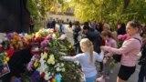 Люди возлагают цветы к монументу в память о погибших при нападении на колледж в Керчи, 18 октября 2018 года