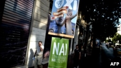 Люди проходять повз плакати з гаслами «так» (NAI) та «ні» (OXI) перед референдумом. Афіни, 3 липня 2015 року
